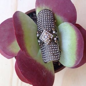 Long carved ring with studs and pearls.